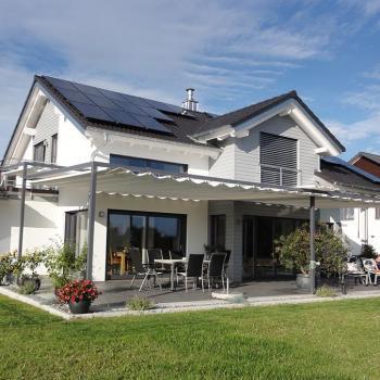 Ein mehrfaches Sonnensegel überdacht ein Wohnzimmer draußen auf der Terrasse.