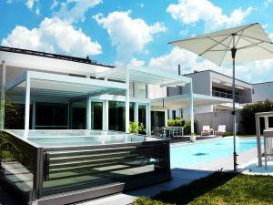 Alles ist quadratisch: die Architektur, der Pool, der Sonnenschirm und das Sonnensegel.