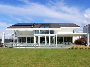 Das moderne weiße Sonnensegel harmoniert mit dem Swimmingpool und der Architektur.