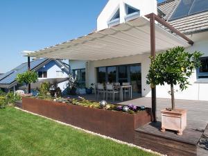 Hier beschattet das VELUSOL Sonnensegel eine schöne Gartenterrasse eines Einfamilienhauses.