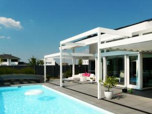 Mit den drei Segeln wird eine große Fläche der Terrasse vor dem Pool beschattet.